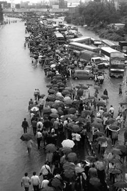 People walk back to their homes as vehicluar traffic came to a standstill due to rains in Bombay.